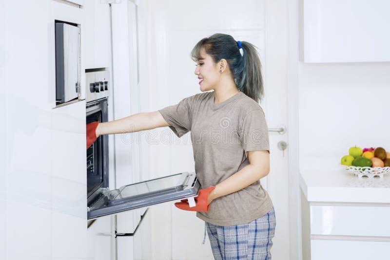 Junge Frau, die ein Backblech in einen Ofen setzt stockfotos