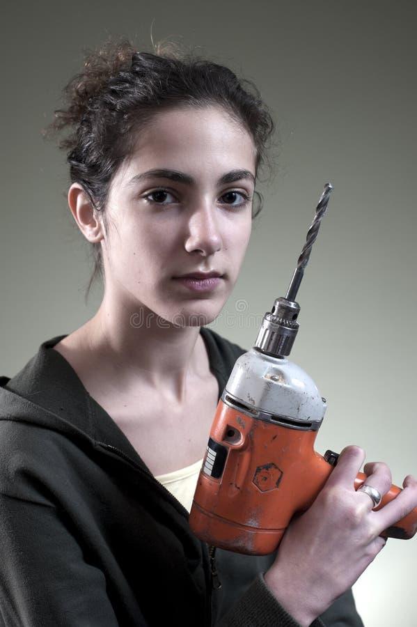 Junge Frau, die ein Bohrgerät hält stockfotografie