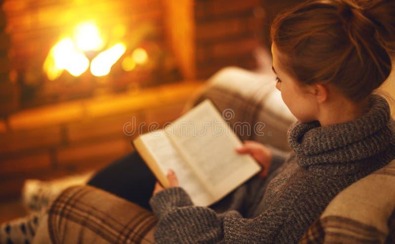 Junge Frau, die ein Buch durch den Kamin auf einem Winter evenin liest stockfotografie