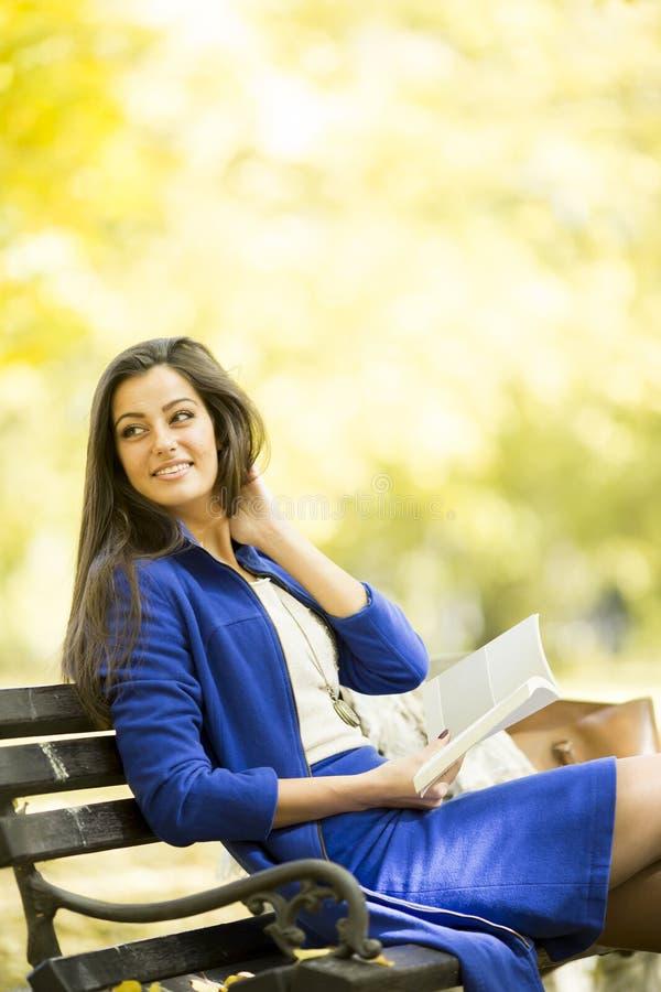 Junge Frau, die ein Buch im Park liest lizenzfreie stockfotografie