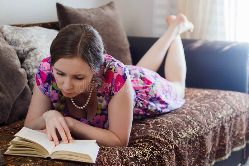 Junge Frau, die ein Buch liegt auf der Couch liest lizenzfreies stockbild
