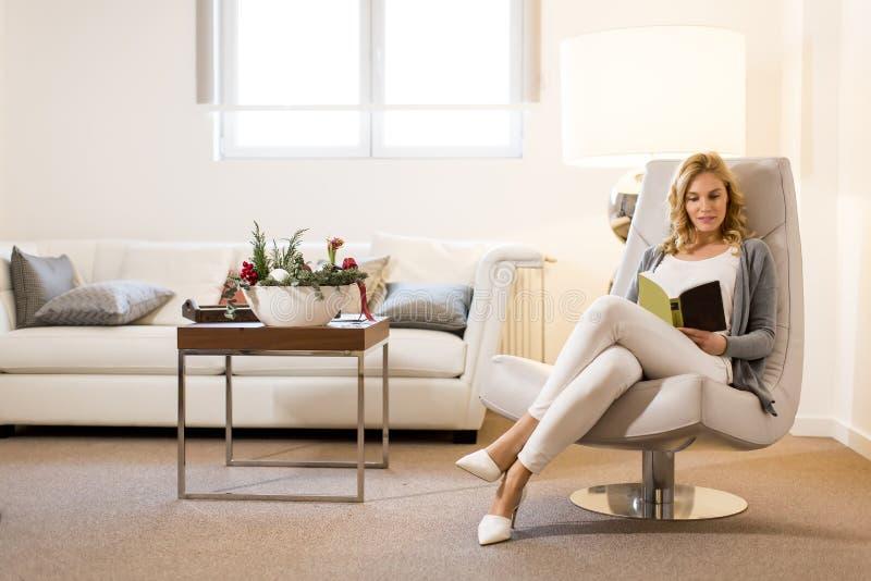 Junge Frau, die ein Buch liest und auf bequemem Stuhl sitzt lizenzfreie stockbilder