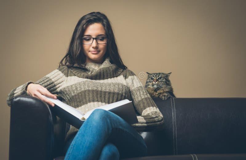 Junge Frau, die ein Buch mit neugieriger Katze liest lizenzfreies stockbild