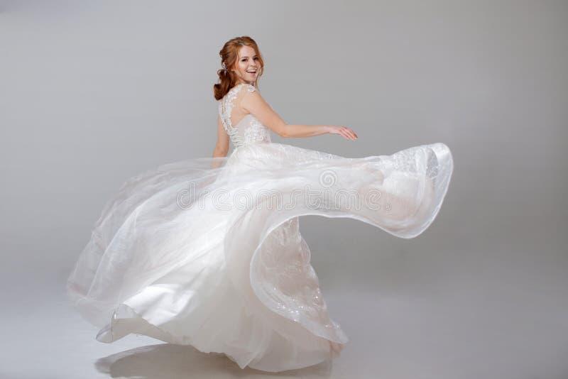 Junge Frau, die in ein curvy Hochzeitskleid spinnt Frauenbraut im verschwenderischen Hochzeitskleid Heller Hintergrund lizenzfreie stockfotos