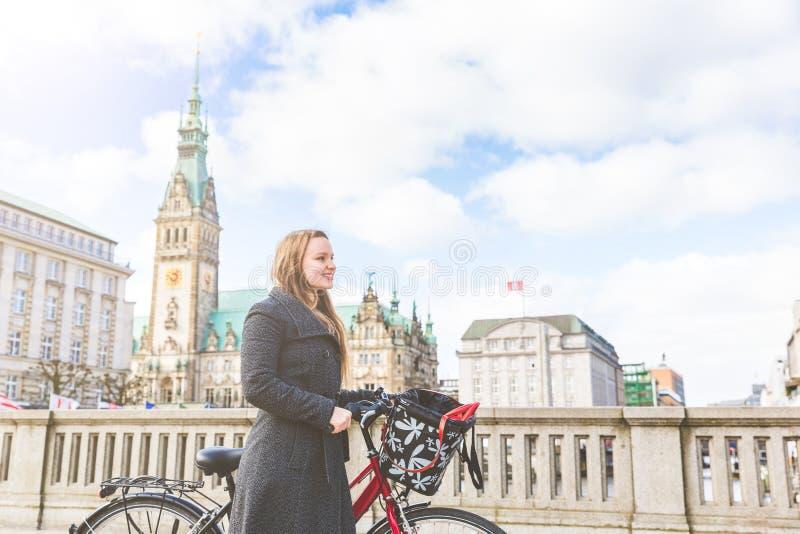 Junge Frau, die ein Fahrrad in Hamburg geht und hält lizenzfreies stockbild