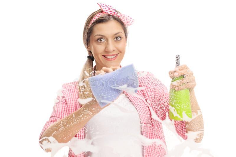 Junge Frau, die ein Fenster mit Tuch und Reinigungsmittel säubert stockbilder