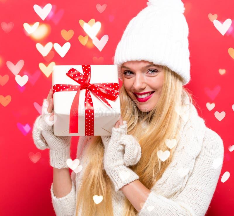 Junge Frau, die ein Geschenk anhält lizenzfreie stockfotos