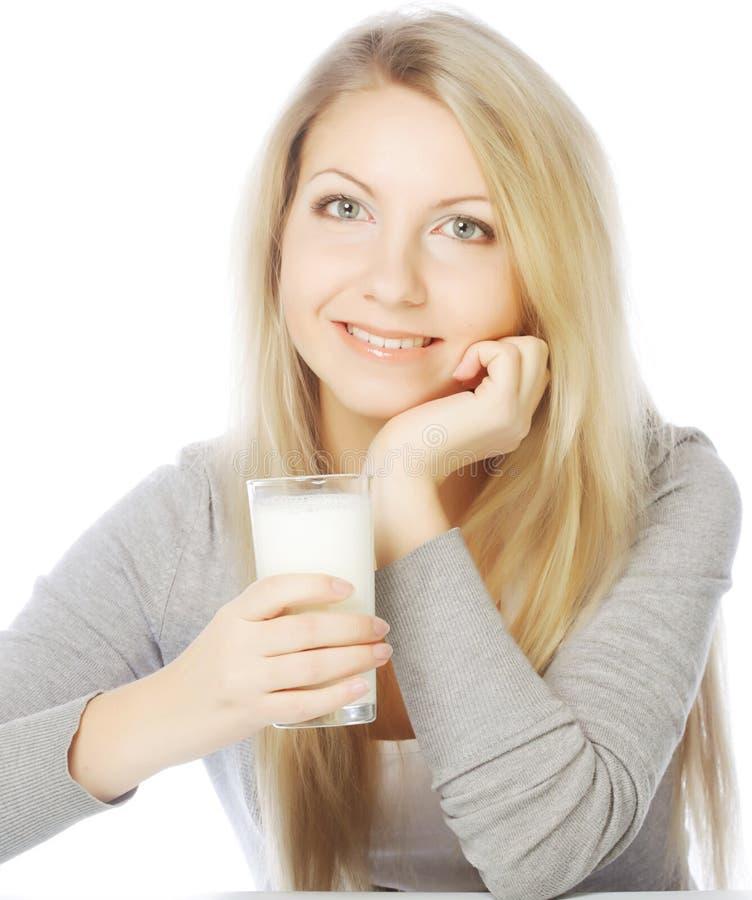 Junge Frau, die ein Glas frische Milch hält lizenzfreie stockfotos