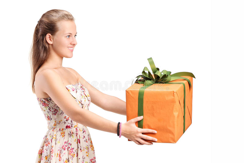 Junge Frau, die ein großes Geschenk hält lizenzfreie stockbilder