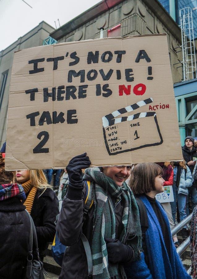 Junge Frau, die ein handgemachtes Plakat mit Slogan während einer Protestsammlung organisiert durch die Jugend-FO-Klimabewegung h lizenzfreies stockbild
