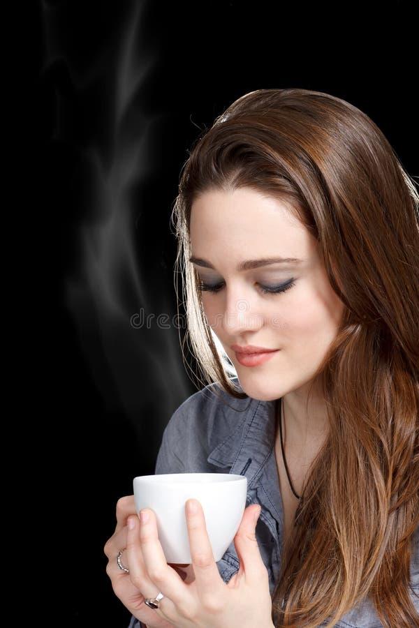 Junge Frau, die ein heißes Getränk genießt stockfotografie