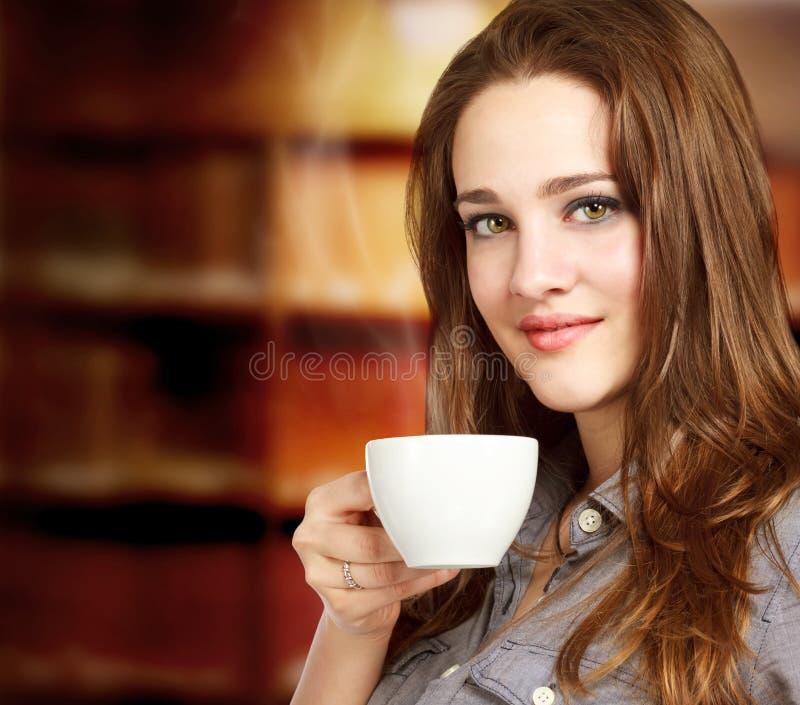 Junge Frau, die ein heißes Getränk genießt lizenzfreie stockfotografie