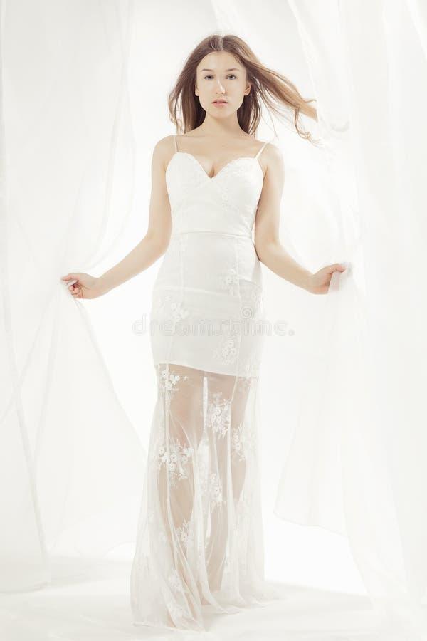 Junge Frau, die ein Hochzeitskleid trägt lizenzfreies stockfoto