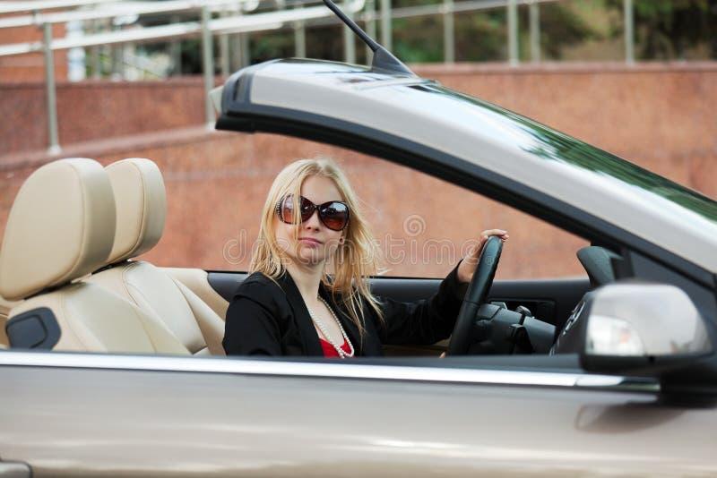 Junge Frau, die ein Kabriolett antreibt. lizenzfreie stockbilder