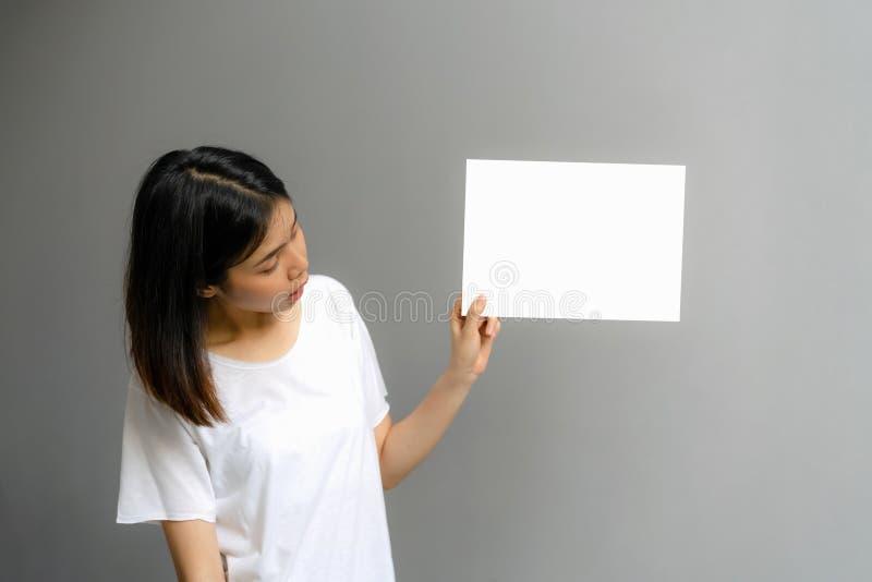 Junge Frau, die ein leeres Plakat f?r Text auf einem wei?en Hintergrund h?lt lizenzfreies stockfoto