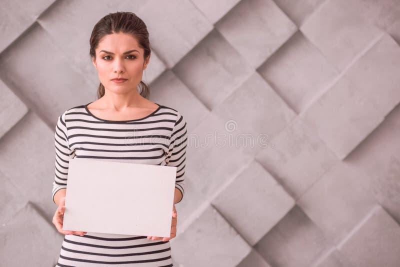 Junge Frau, die ein leeres Plakat ohne Text hält stockfotografie