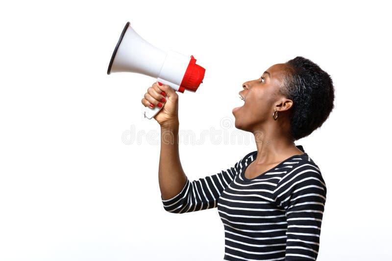 Junge Frau, die in ein Megaphon schreit lizenzfreies stockfoto