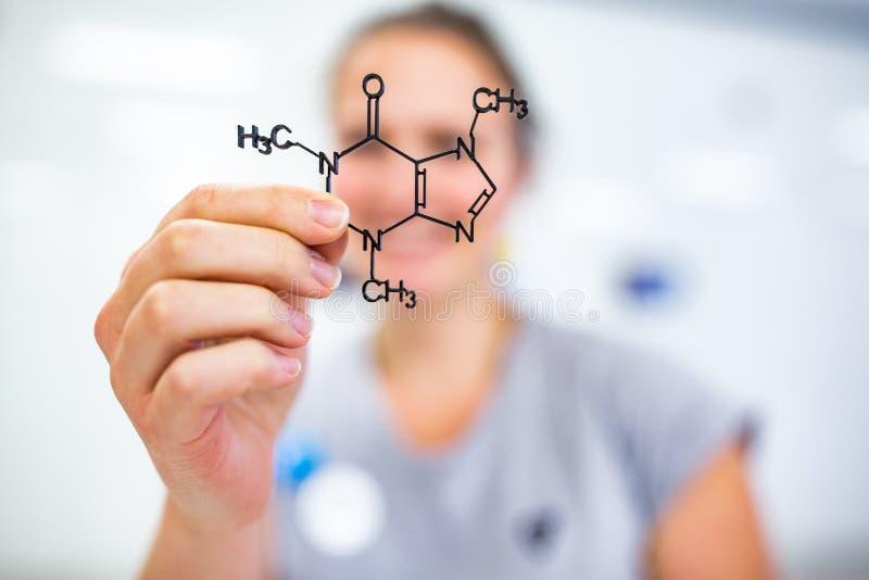 Junge Frau, die ein molekulares Modell hält lizenzfreies stockbild