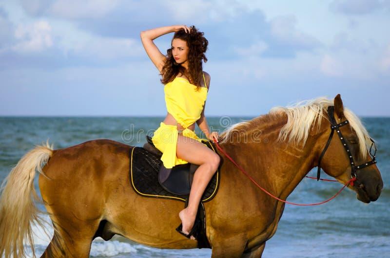 Junge Frau, die ein Pferd reitet stockfotos