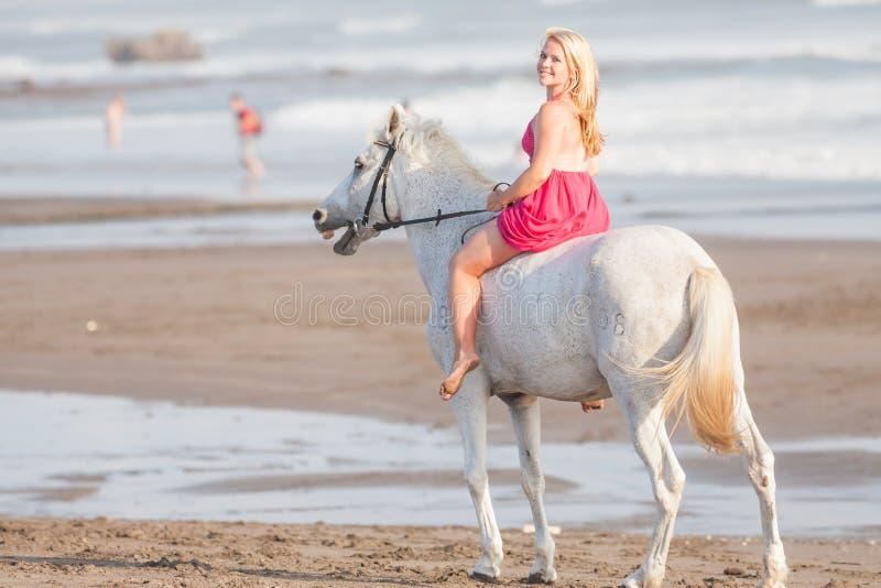 Junge Frau, die ein Pferd reitet stockbilder