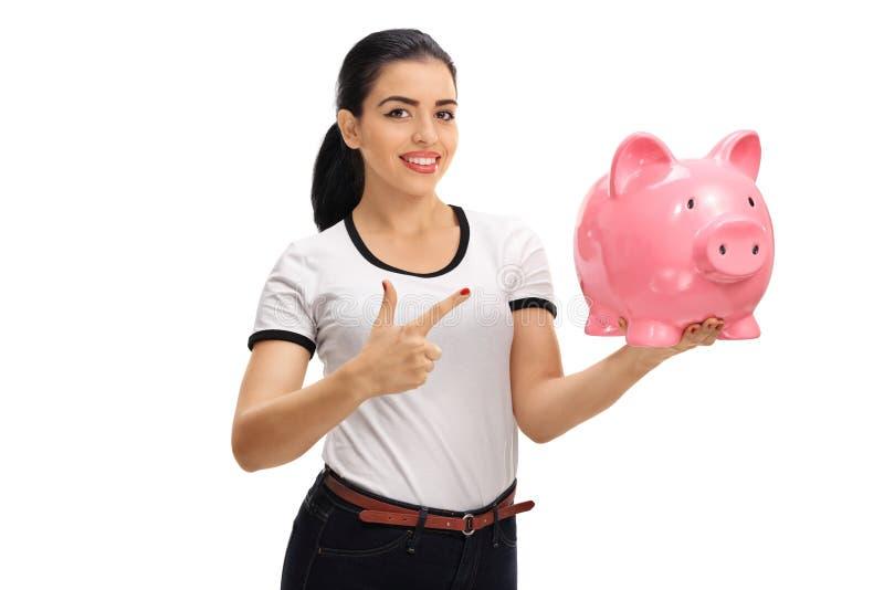 Junge Frau, die ein piggybank und ein Zeigen hält lizenzfreies stockfoto