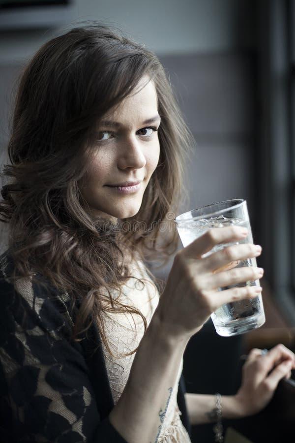 Junge Frau, die ein Pint-Glas Eis-Wasser trinkt stockfotos