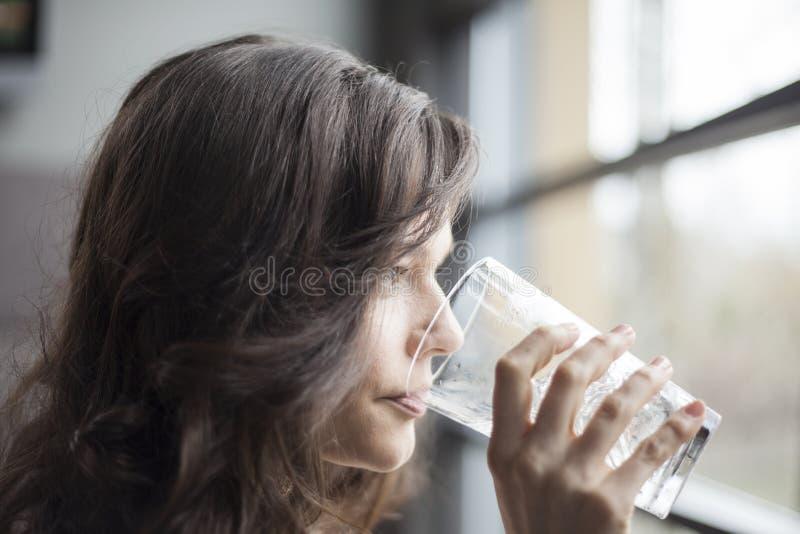 Junge Frau, die ein Pint-Glas Schmelzwasser trinkt lizenzfreie stockfotografie