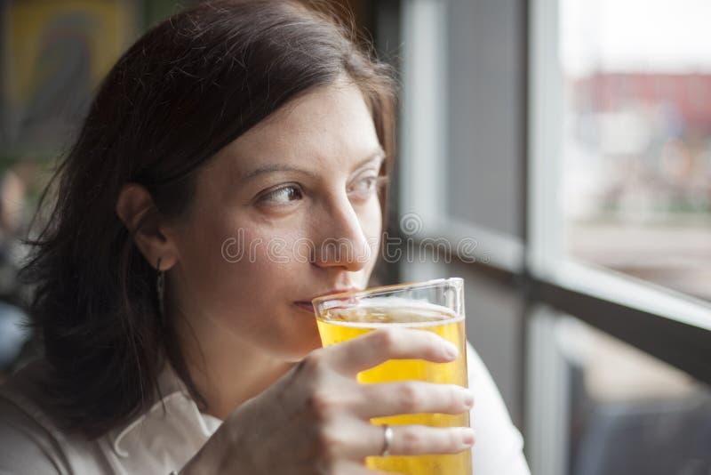Junge Frau, die ein Pint harten Apfelwein trinkt lizenzfreies stockfoto