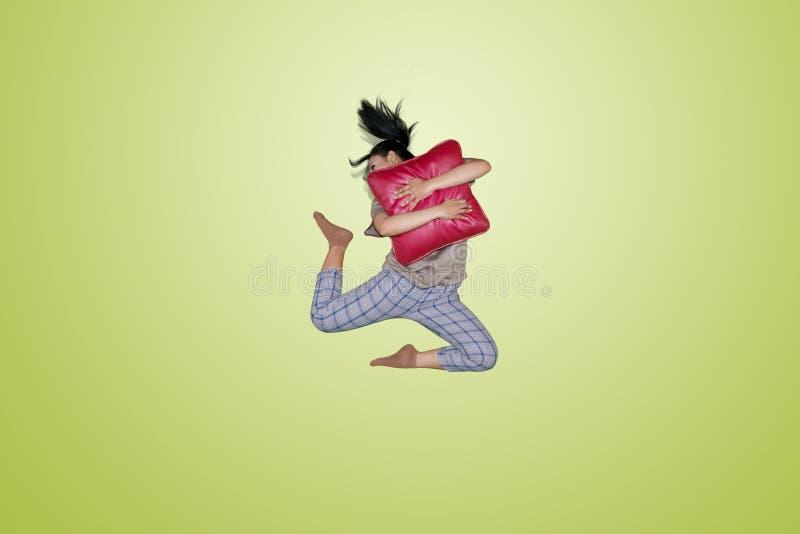 Junge Frau, die ein rotes Kissen springt und umarmt stockfotos