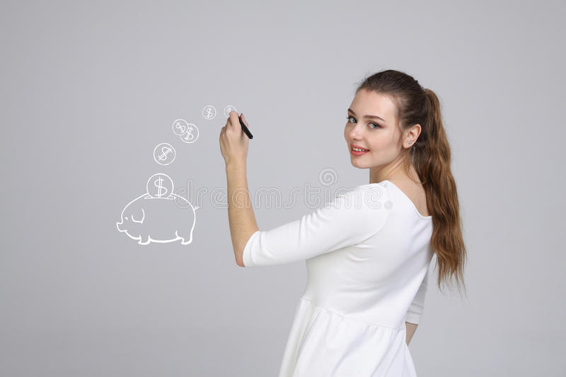 Junge Frau, die ein Sparschwein zeichnet stockfotografie