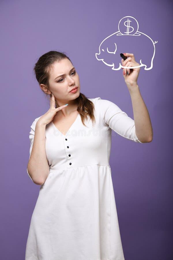 Junge Frau, die ein Sparschwein zeichnet lizenzfreies stockfoto
