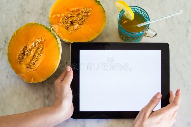 Junge Frau, die ein Tablet mit Modellschirm mit den Händen auf einer Tabelle mit Sommerfrucht und -getränk hält stockbild