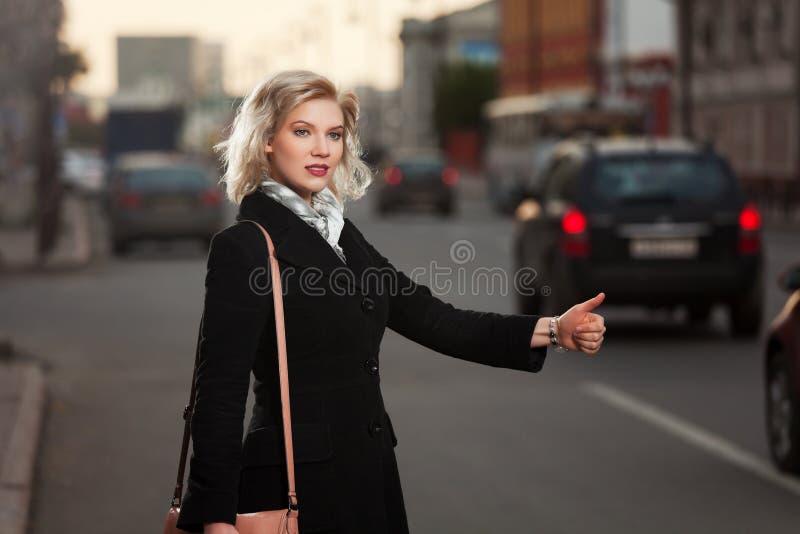Junge Frau, die ein Taxi hagelt lizenzfreie stockbilder