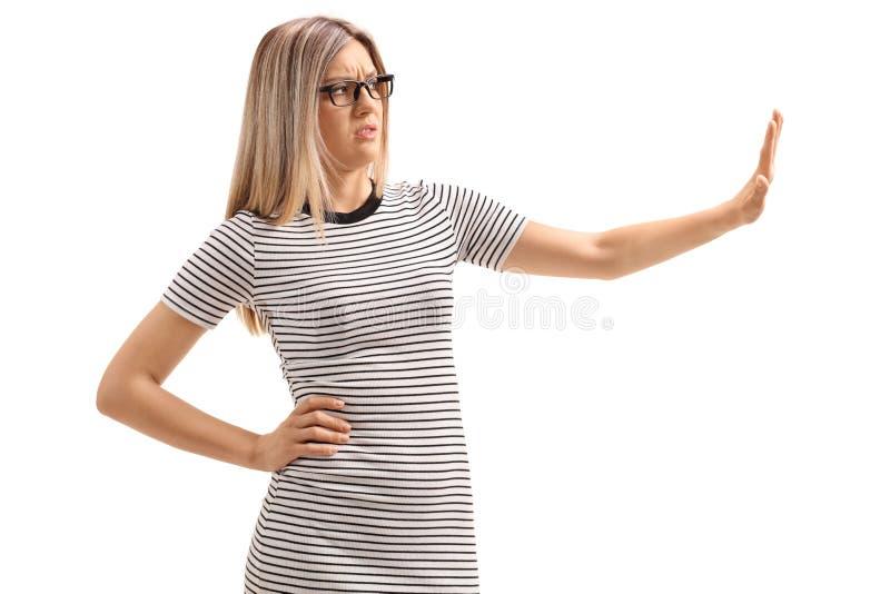 Junge Frau, die eine Abfallgeste mit ihrer Hand macht stockbilder