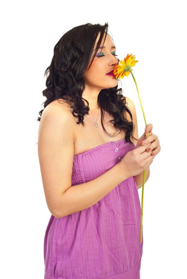 Junge Frau, die eine Blume riecht stockbild
