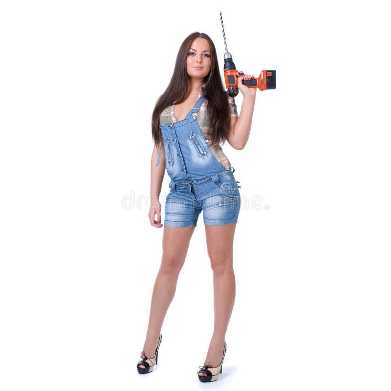 Junge Frau, die eine drahtlose elektrische Bohrmaschine hält Lokalisiert auf Weiß stockfotografie