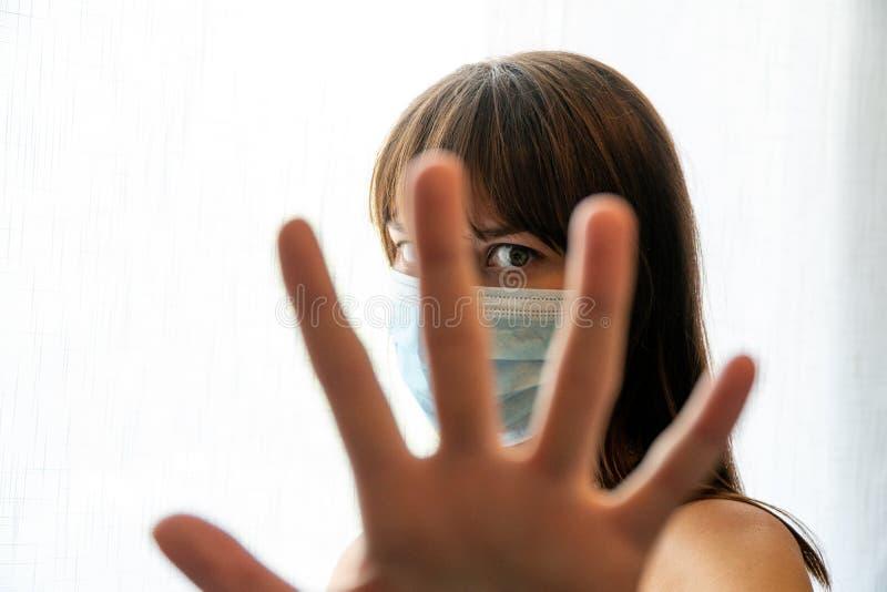 Junge Frau, die eine Einwegmaske trägt, die mit einer Geste aufhört, durch die Finger zu schauen stockbilder