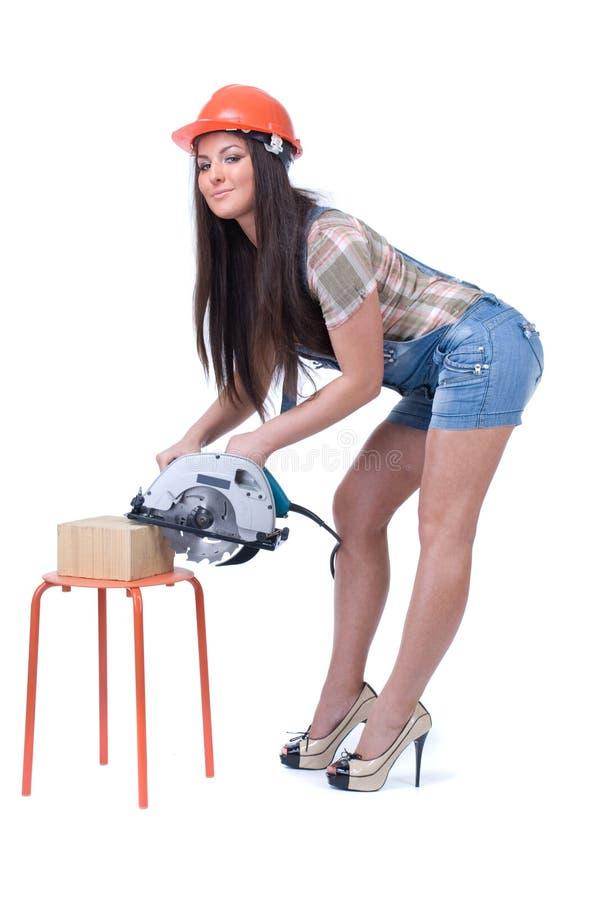Junge Frau, die eine elektrische Kreiskreissäge hält lizenzfreie stockbilder