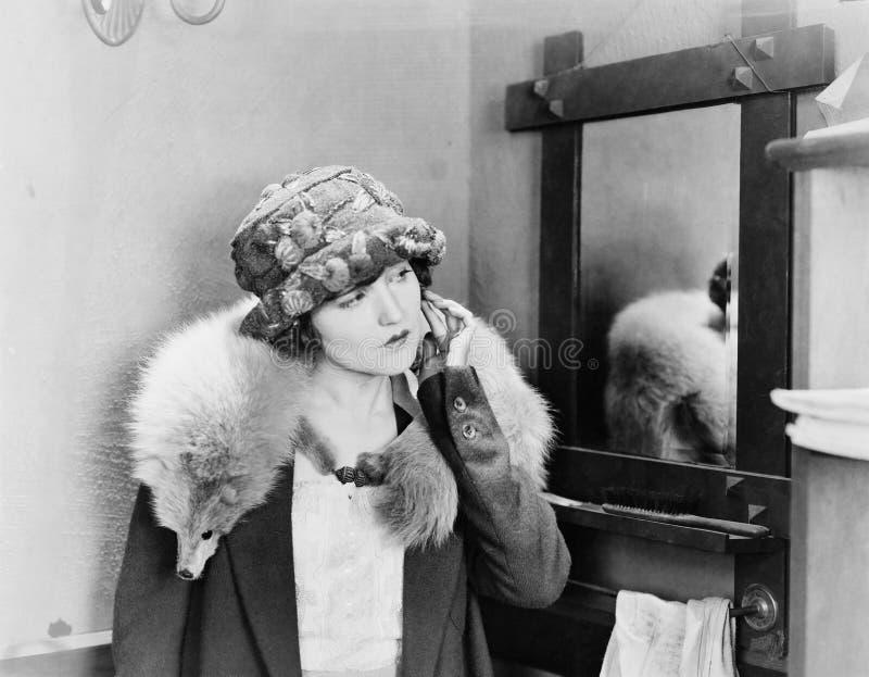 Junge Frau, die eine Fuchsstola auf ihren Schultern trägt und ihren Ohrring justiert (alle dargestellten Personen sind nicht läng lizenzfreie stockbilder