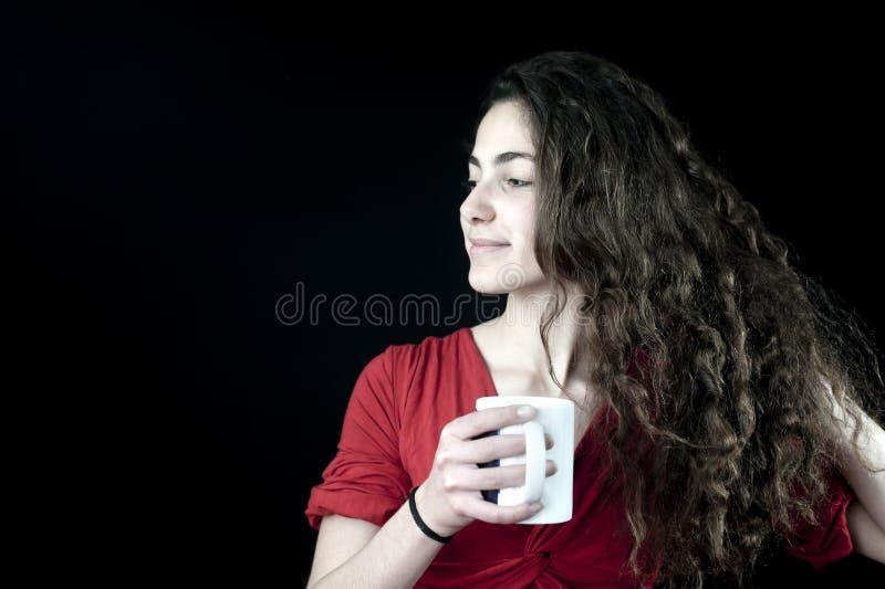 Junge Frau, die eine Kaffeetasse anhält lizenzfreie stockbilder