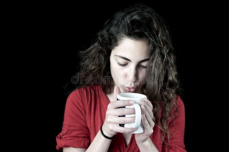 Junge Frau, die eine Kaffeetasse anhält stockfoto