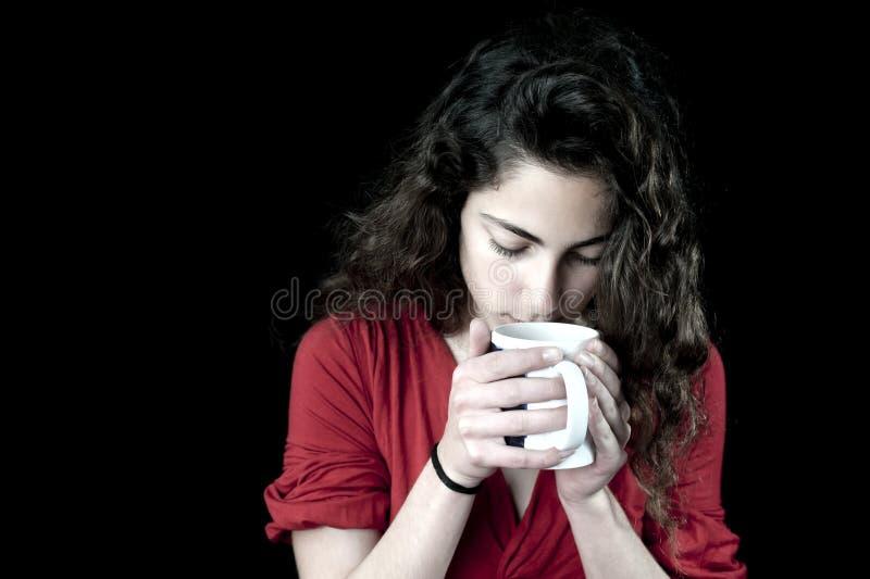 Junge Frau, die eine Kaffeetasse anhält stockbild