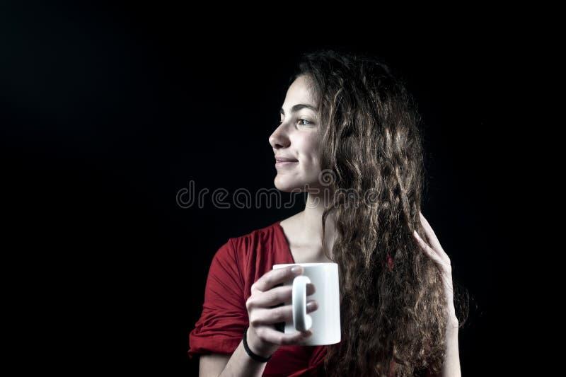 Junge Frau, die eine Kaffeetasse anhält lizenzfreies stockbild