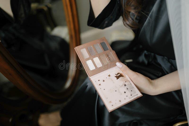 Junge Frau, die eine Make-uppalette in ihrer Handnahaufnahme hält stockbilder
