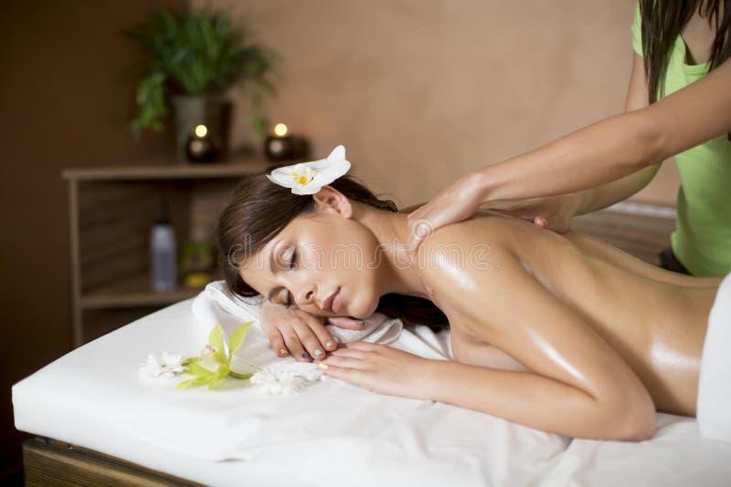 Junge Frau, die eine Massage in der Badekurortmitte erhält stockfotografie