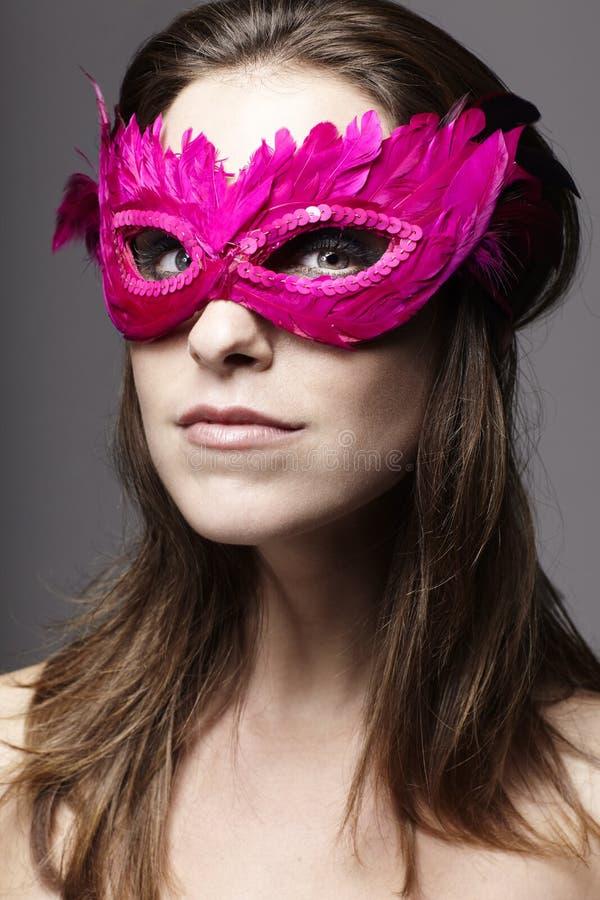 Junge Frau, die eine rosa Federmaske trägt stockfotos