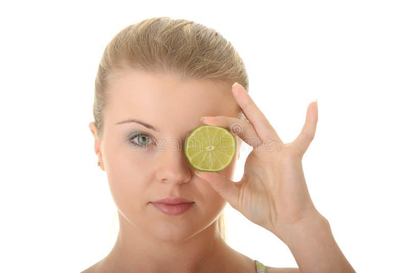 Junge Frau, die eine Scheibe der Zitrone anhält stockbild