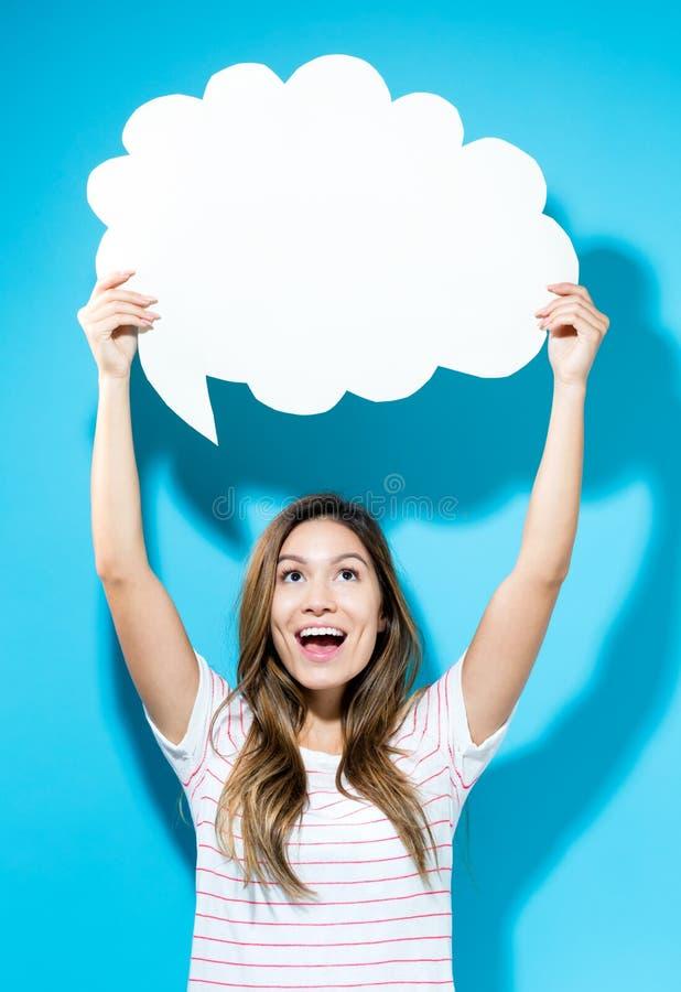 Junge Frau, die eine Spracheblase hält lizenzfreies stockbild
