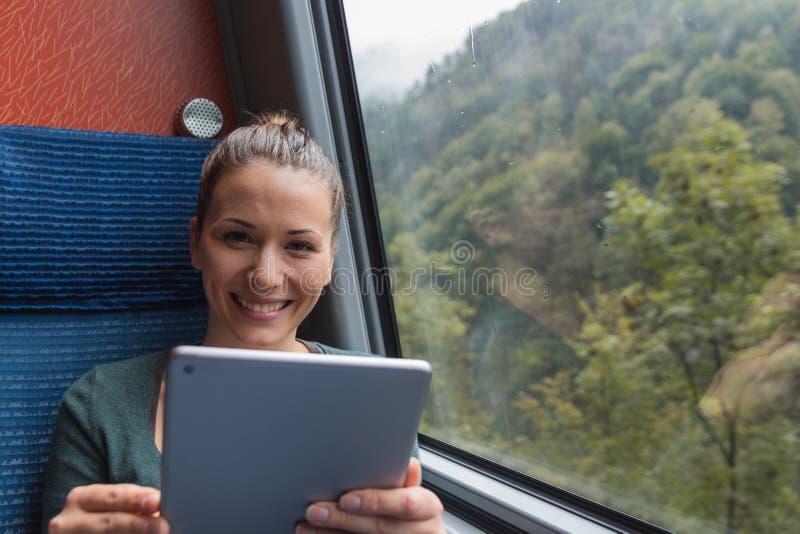 Junge Frau, die eine Tablette für das Studieren beim Reisen mit dem Zug lächelt und verwendet lizenzfreie stockfotografie