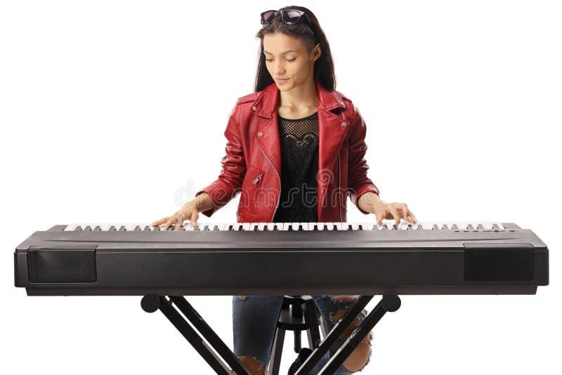 Junge Frau, die eine Tastatur spielt stockfotos